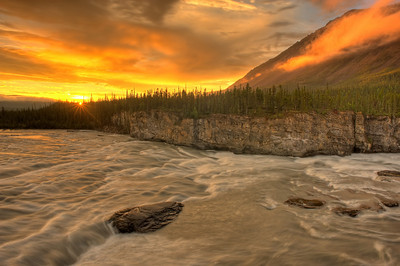 Orange sunset on Sluicebox rapids above Virginia Falls, one of Canada's largest waterfalls. Nahanni National Park is one of the world's top paddling/canoeing rivers, and Unesco World Heritage site. The Nahanni River is also a Canadian Heritage River. Northwest Territories (NWT) Canada.