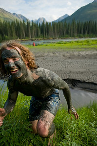 Brian Pollock frolicking in the lush grasses of Moore's Hot Springs. Covered in mud and full of excitement and energy.  Nahanni National Park is a Unesco World Heritage site. The Nahanni River is also a Canadian Heritage River and one of the world's most popular paddling/canoeing destinations. Northwest Territories (NWT) Canada.