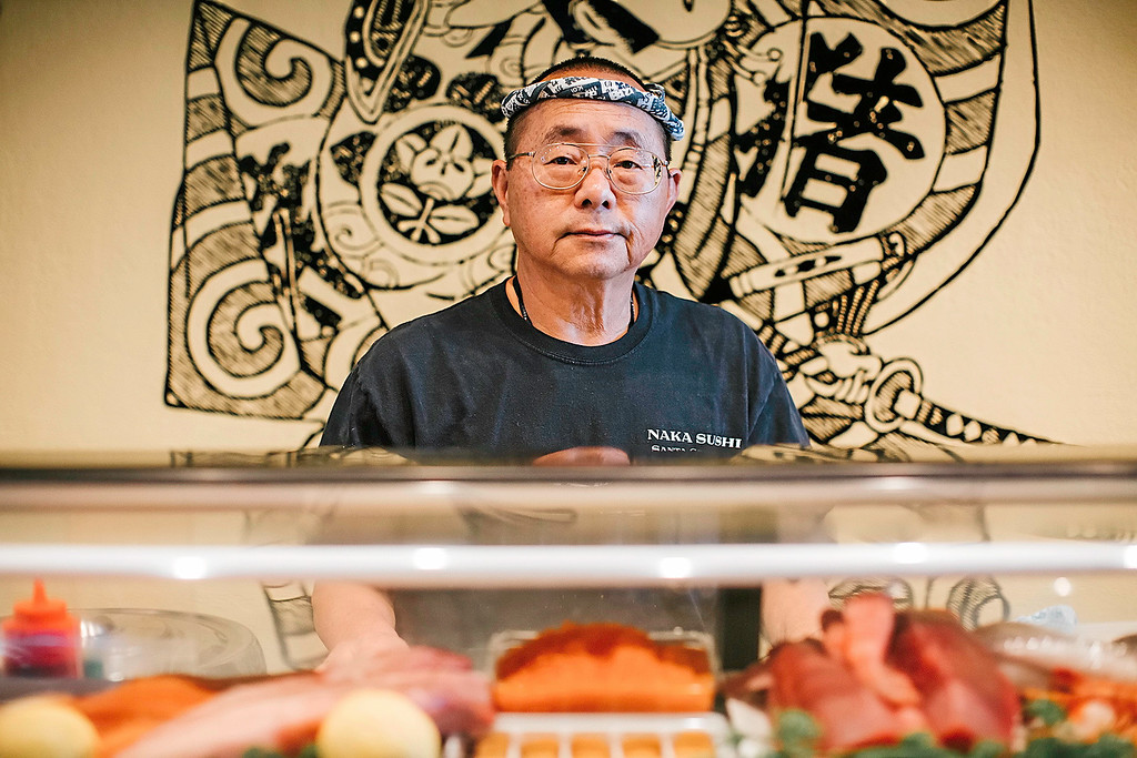 . Owner and sushi chef Masao Nakagawa poses for a portrait in front of his work space which is meticulously organized with tools and colorful ingredients. (Carolyn Kelley - Santa Cruz Sentinel)
