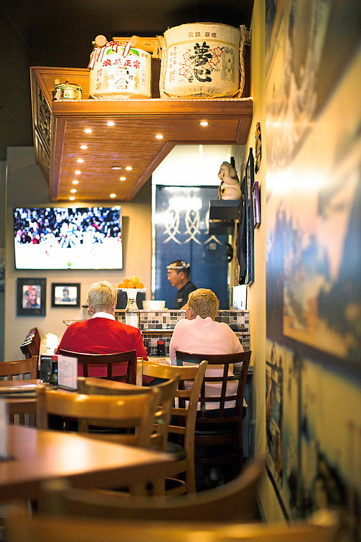 . After the doors open, the first customers head straight for the sushi bar to relax with drinks and a view of the Sumo matches that play on a nearby tv. (Carolyn Kelley - Santa Cruz Sentinel)