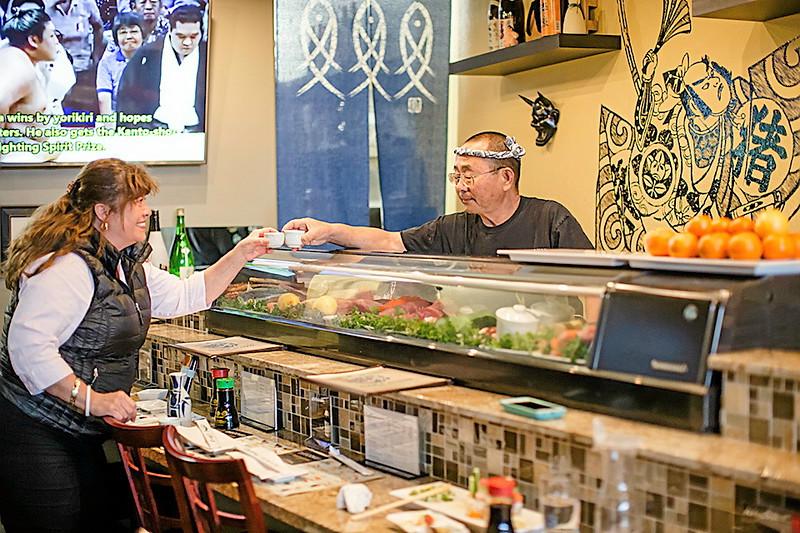 . Owner Masao Nakagawa accepts a gift of sake from a customer at his new restaurant Naka Sushi in Capitola. (Carolyn Kelley - Santa Cruz Sentinel)