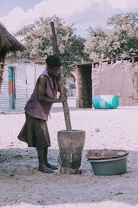 woman crushing the millet, Africa, Namibia