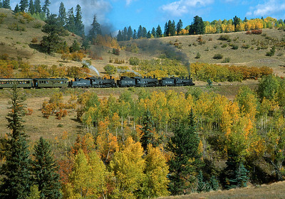 October 2000.   One of the last three engine fall color trains.  Three classes of engines, the 487, 497 and 463 lead the regular train up the 4 percent climb to Cumbres summit through a riot of fall color.