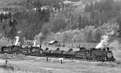 October 1997.  A passenger train passes a chartered freight in the siding at Lobato.