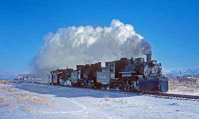 December 1961. A flanger spreader train hustles down the three rail between Alamosa and Antonito to clear snow over Cumbres ahead of a following freight.