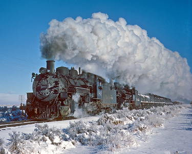 A fresh snow covers the San Luis Valley as this DRGW ng. freight heads south from Alamosa on the three rail branch to Antonito. At Antonito the helper will be cut into the train for the climb to Cumbres. December 18, 1961.