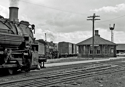 Antonito. Lots of interesting stuff in this image. Two engines, three rail track, dual gauge switch, switching a standard gauge car with an idler flat, the stone Antonito station, train order signal.  September 1960.