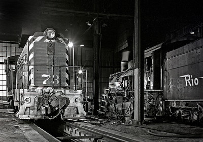 The standard gauge diesel switcher and the narrow gauge 2-8-2 spend a night together in the Alamosa roundhouse. Note the adjustable coupler on the switcher, so that it could handle both narrow gauge and standard gauge cars on the dual gauge track in the yard.  Circa 1965.