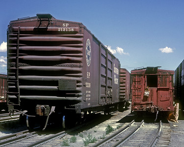 Alamosa, July 1963.  The water bag hanging from the end of the narrow gauge boxcar is good evidence of the amount of manual labor involved in the transloading.  It was an expensive inefficiency associated with the continued operation of the narrow gauge.
