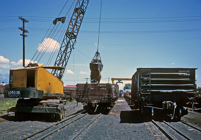 Alamosa, July 1963.  Some of the transloading  action.  In addition to the bucket transloading sand from the standard gauge gon to the narrow gauge gon, in the background is the overhead crane used to transload pipe.