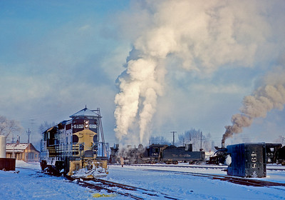 December 18, 1961.   Cold morning in Alamosa.  The 480 and 488 have topped off with coal and sand, and are heading for the plug for water.  Soon they will be leaving town with a freight for Chama.