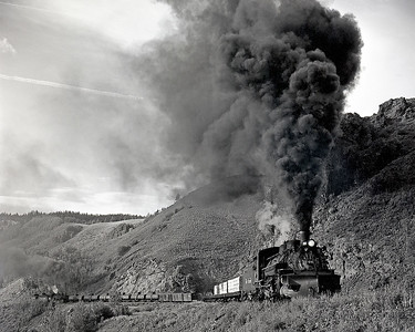 July 1964. The 488 with a Cumbres turn really smokes it up as it climbs the final 4 percent around Windy Point to the pass. As was normal practice, a helper is cut in ahead of the caboose in the distance. Typically two Cumbres turns would be made with two (or before 1959 three) engines. The following morning a third cut would be hauled up the hill and then a 70 car train put together behind one engine for the long downhill run from Cumbres to Alamosa.