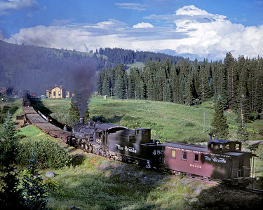 July 23 1963. DRGW 488 patiently waits its turn at Cumbres while the road engine takes water. Note the snowshed, now gone.