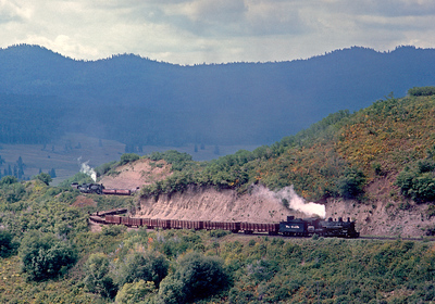 A Cumbres turn approaches the west switch to Cresco siding while climbing to Cumbres. The cars will be left at Cumbres and the engines and caboose will return to Chama. After spending another night in Chama the crew will take a third cut to the top tomorrow, put it all together in one long 60-70 car train, and one engine will take the train down the hill to Alamosa while the helper runs ahead light.  September 1964.
