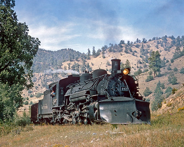 September 15, 1965.  Engineer Bill Holt eyes the photographer as the 487 rolls east with a short train around MP 384 east of Juanita.  In the old days this was about as far as you could go from the west in a car.  From here to Navajo was pretty much a  rough 4x4 trail..