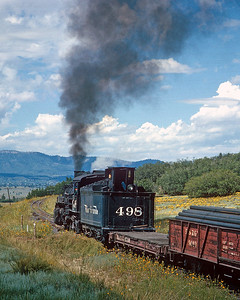 September 1964.   The head brakeman relaxes in the dog house as the 498 climbs out of Willow Creek headed for the Continental Divide near Azotea, just west of Chama.