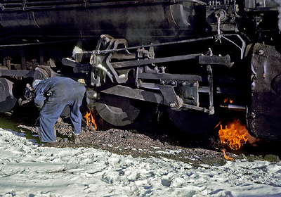 "December 1961. The temps are way below freezing during the night, steam engines tend to drip, ice forms, and the result by early morning is an engine solidly frozen to the rails. So the hostler burns some oil soaked waste along side the wheels to loosen things up. Gives a whole new meaning to the term ""hot rail""."