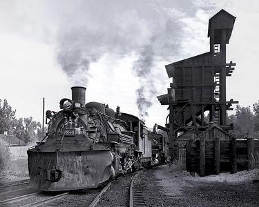 DRGW 484 and another engine are serviced at the Chama coaling tower in preparation for a trip west to Durango. This coaling tower still exists on the C&TS and while it is not used it is very close to being serviceable and may be used in the future on a demonstration basis.  July 1963.