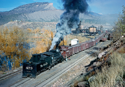 October 1962. The 473 switches an inbound train at the east end of the Durango yard. The boxcars were probably empties that would be spotted at the lumber mill for loading. Note the 473 is equipped with footboards and a power reverse as required by the ICC at that time for switch engines, so it is the regularly assigned Durango switcher. But it also has the fake diamond stack if needed for Silverton service.