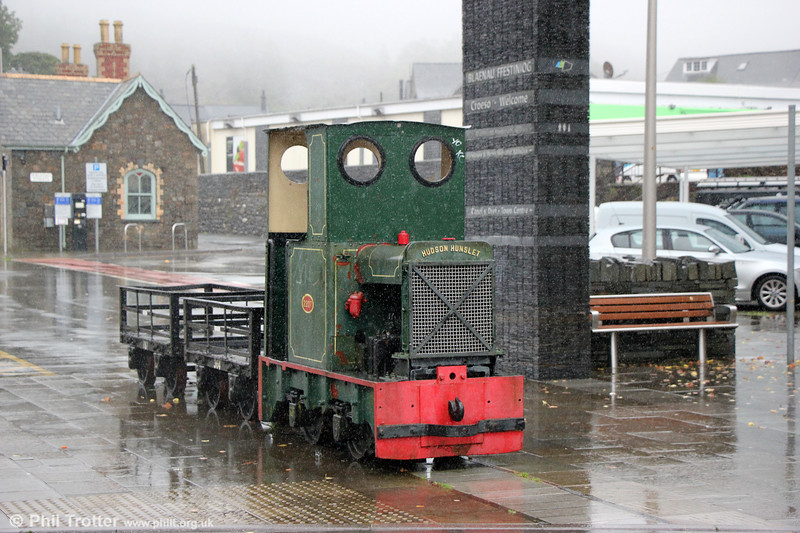 Hunslet 2207 is a 2ft gauge 4wDM of the 'Hudson-Hunslet' type (built by Hunslet for sale through Robert Hudson Ltd) that was new to the Trefor (Yr Eifl) Granite Quarry on the Lleyn Peninsula in 1941. Disposed of for preservation in 1965, it later found its way to the Gloddfa Ganol collection housed at Oakeley Slate Quarries in Blaenau Ffestiniog. In July 1979, it was placed on display adjacent to the Ffestiniog Railway station in Blaenau Ffestiniog. Under the care of Gwynedd Council, it remained there until removed to the Ffestiniog Railway around December 2011 for cosmetic restoration. It was returned to Blaenau on 12 October 2012, having been cleaned up, repainted and varnished. It is now in a slightly different location that places it on an alignment with the former FR mineral line through Duffws station (the building in the background) and is accompanied by two FR slate wagons, 364 and 787. 5th September 2017.