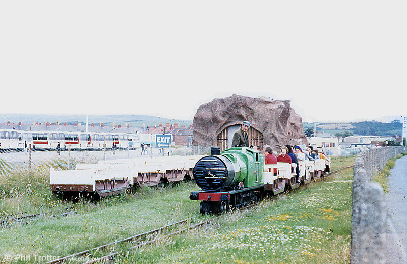 A photograph taken at approximately the mid point of the Porthcawl Miniature Railway. The line itself was single  with a loop in the middle; the engine shed was disguised as a tunnel. <br /> <br /> The train that was originally used consisted of 'Silver Jubilee'; a steam outline petrol powered 4-6-4 loco with a hydrostatic transmission that was originally used to operate the periscope on a WW1 submarine. The original train consisted of 6, 4 wheel, open coaches that used carriage under frames from the Romney, Hythe and Dymchurch Railway in Kent. One interesting fact is that the loco always faced Coney Beach because it only had one cab door cut out which was on the road side of the railway. <br /> <br /> In 1936 a second train was acquired. This being 'Coney Queen' (above) plus a train of articulated stock to the same pattern as the 4 wheelers already owned. In later years, certainly by the '60's, the 4 wheelers were behind 'Coney Queen' and the artics behind 'Silver Jubilee'.