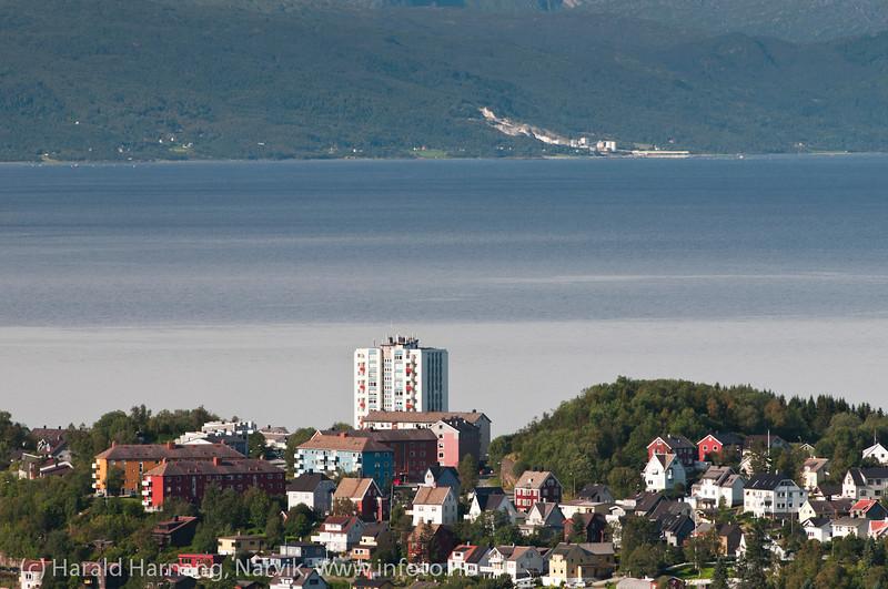 Høyhus på Framnes, fotografert fra Taraldsvikfoss kraftstasjon. Helt i bakgrunnen dolomitt-brudd ved Hekkelstrand i Ballangne kommune. Oversiktsbilde Narvik. August 2012.