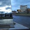 Fredsmonument i Narvik sentrum i forgrunnen speiler sørhimmel og tribune. I bakgrunnen Narvik rådhus med juletre foran. Til høyre E6.