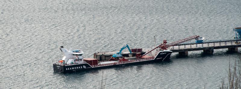"""Olivinskip """"Helene W II"""" ankom Narvik og gamle kai 3-4 for lossing av olivin. Få sekunder etter at skipet klappet til kai, var lossingen i gang. Grabb midt på legger ned i transportbånd som går helt inn på land. 7. mars 2014."""