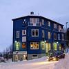 Tidligere var det avishus fra loft til kjeller, nå ymse annet. 3. juledag 2014. Snevær på natta. Mørketid og en julestille by.