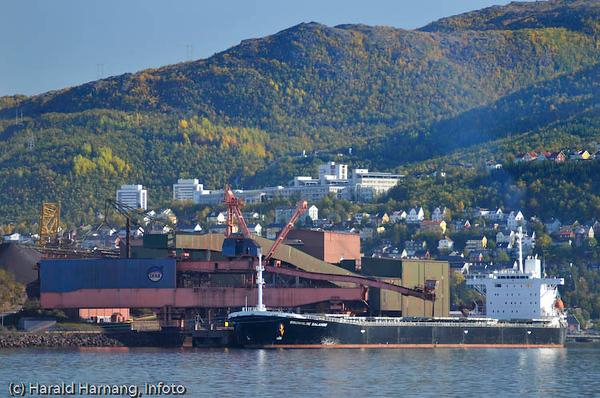 Lite malmskip ved kai 5 laster malm. I bakgrunnen Høgskolen i Narvik, samt tre boligblokker.