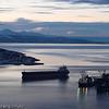 Et malmskip er under lasting ved kai 5, LKABs anlegg, mens et nytt skip er på tur inn på havna. Mørketidsbilde. Til venstre Ankenes. Ofotfjorden ut mot høyre.