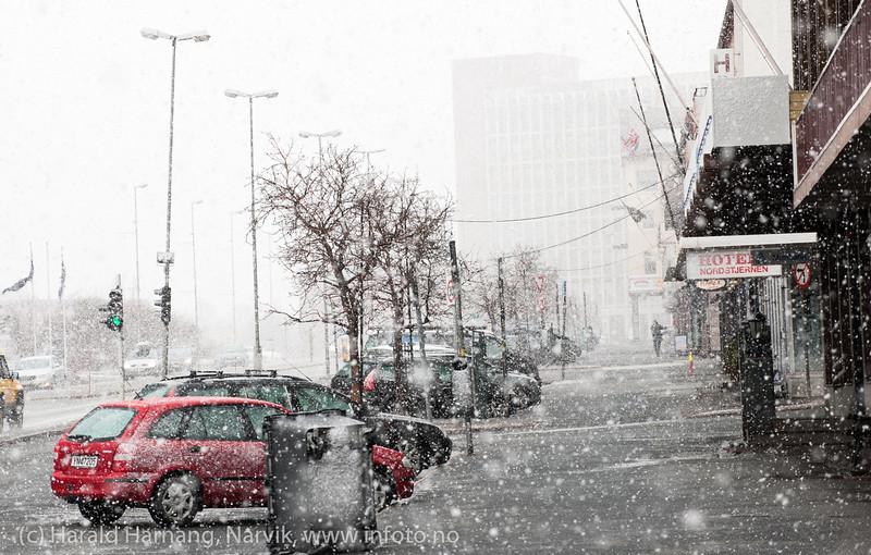 """E6-Kongens gate Narvik 14. mars 2014. Tippet søppelcontainer og en enslig sjel å se. Ekstremværet """"Kyrre"""" kommer med vind og snø. Som vanlig gikk det pent for seg innerst i Ofotfjorden."""