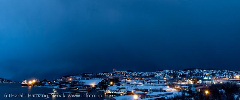 Mørketid 27.desember 2011. Mørke skyer med snøbyger i det det blir mørkt kl 1430.  Til venstre LKABs utlastingsanlegg (kai 5).