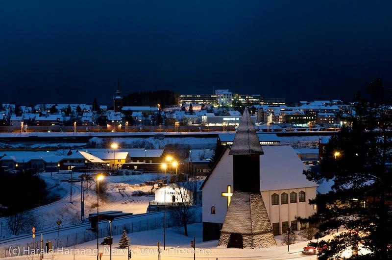 Sjømannskirka i Narvik i forgrunnen. Bak til venstre Narvik kirke. Bak sykehus. Mørketid 27. desember 2011 kl 1430. Snøbyger og uvær bygger seg opp bak.