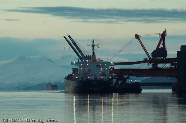 Et malmskip er under lasting ved kai 5, LKABs anlegg, mens et nytt skip kommer inn fjorden. Mørketid.