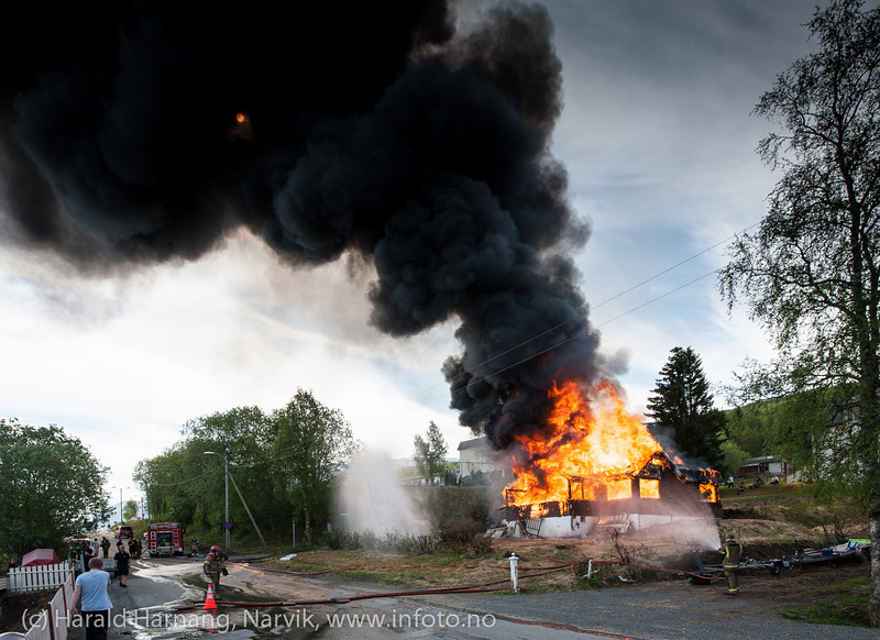 Kontrollert nedbrenning av hus på Ankenes. Sola skinner såvidt gjennom røyken.