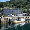 Havnens hus, fiskebåt i forgrunnen, midt på kjøres et vognsett med malmvogner forbi.