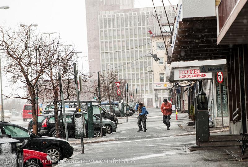 """E6-Kongens gate Narvik 14. mars 2014. To som bakser seg frem i vinden. Ekstremværet """"Kyrre"""" kommer med vind og snø. Som vanlig gikk det pent for seg innerst i Ofotfjorden."""