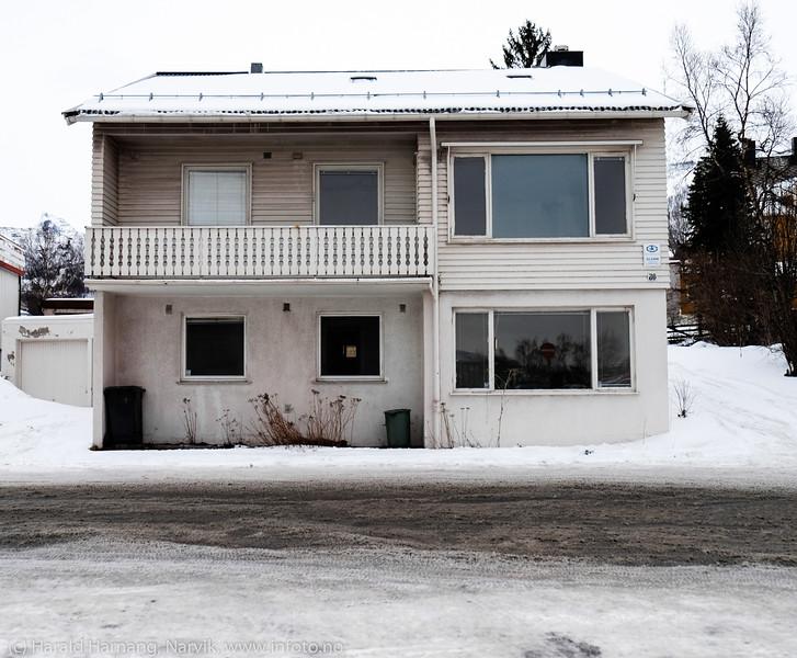 I skyggen av et kjøpesenter: Hus rett bak Narvik Storsenter. Lys fra alle bilene som kjører ut av kjøpesenterets P-plass sendes rett inn i stue og kjøkken. Tilnærmet uboelig. Dronningens gate 80. 27. mars 2015.