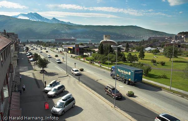E6, Kongens gate gjennom sentrum av Narvik. Til høyre Parkhallene med grøntanlegg på toppen. Utendørs-scene midt på. Havna med malmskip bak.