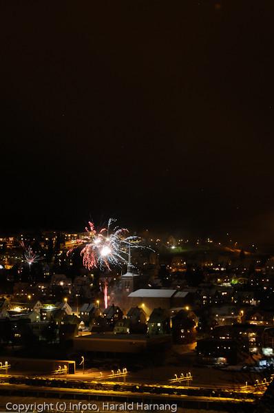 """Nyttårsaften kl 2345, år 2010. Bakkefyrverkeriet er ikke like spektakulært og høyt på himmelen som de """"gode"""" gamle (og farlige) rakettene. Foto av fyrverkeri nær Narvik kirke. Foto fra Oscarsborg. Svart himmel over."""