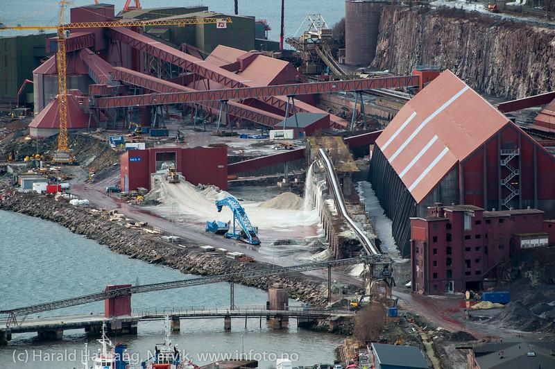 Olivin-området til LKAB (hvit stein). Vi ser transporbåndet fra skipet tømmes ned på bakken. Herfra lastes med doser ned i sjakt, omlag midt på bildet. 7. mars 2014.