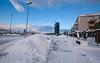 Kongens gate nordover, fra omlag Kongens gate 18 (tidligare post og politihus). Statue til høyre. Scandic hotell midt på. Stor snøhaug som hindrer utsikten i tverrgata. Narvik kirke til venstre.