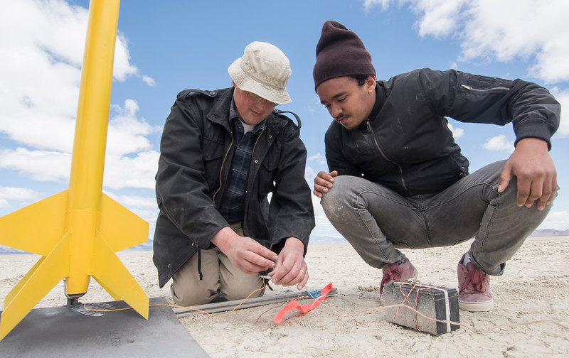 Mike Harrell, left, the rocketry program advisor, and Adonay Lebeneh wire a rocket before it is launched in Black Rock Desert, Nev. on May 1, 2016.