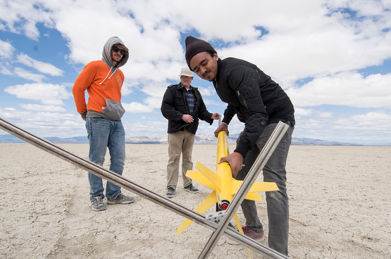 Adonay Lebeneh, right, slides his rocket onto the launching platform as Mike Harrell, center, the rocketry program advisor, and Gabe Finertie assist in Black Rock Desert, Nev. on May 1, 2016.