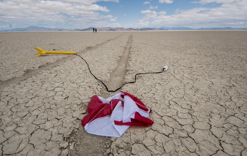 A deployed rocket lays on the ground with a parachute as students walk to retrieve it after being launched in Black Rock Desert, Nev. on May 1, 2016.