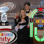 Brad Keselowski, Paige White, and their daughter, Scarlett, posed with the Kentucky 300 trophy and the Crosley jukebox that awaited the race winner.