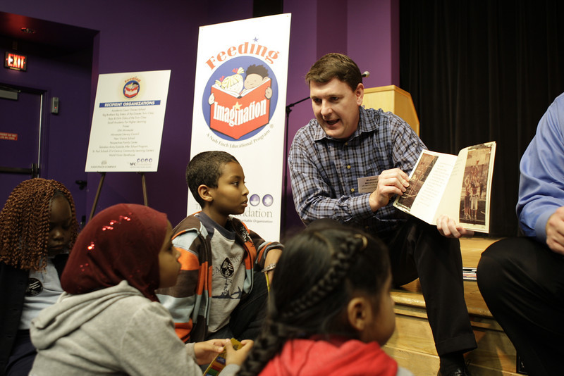 Minneapolis, MN - Jeff Poore, right, and Blaine McGuire, center, read a book to local school children who took part in the Feeding Imagination Celebration honoring the 2nd year of books donated to local schools and organizations by the Nash Finch Company Charitable Foundation here today, Thursday November 20, 2008. The Feeding Imagination program has donated over 60,000 books to local organizations in the last 2 years and announced 12,000 more books to be donated to 12 organizations today. Date: Thursday November 20, 2008 Photo by © Todd Buchanan 2008 Technical Questions: todd@toddbuchanan.com; Phone: 612-226-5154.