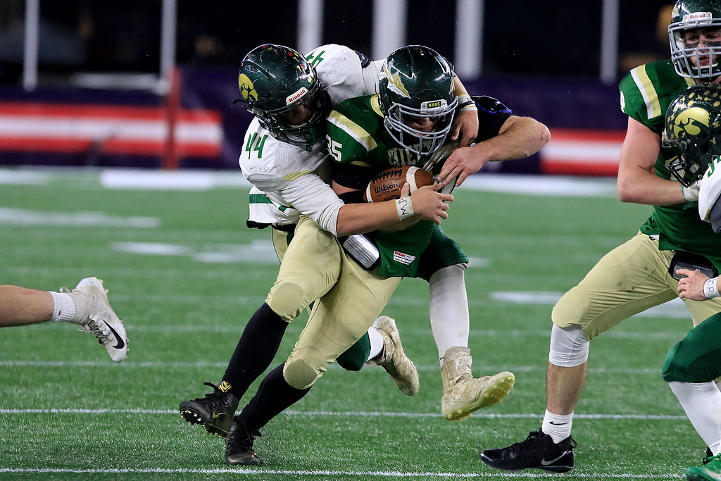 . Nashoba Regional High School\'s Alex Childs is tackled by  Dighton-Rehoboth Regional High School Chase Carroll at Gillette Stadium in Foxborough on Friday night, November 30, 2018. SENTINEL & ENTERPRISE/JOHN LOVE