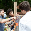 Nashoba Valley Technical High School carpentry instructor Jonathan Pryor (left) works on a bed constructed by his students, including Jonathan Suero (center) of Pepperell and Tyler Alden (right) of Chelmsford. Lowell Sun/Chris Lisinski